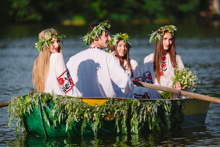 Midsummer. A group of young people in national costumes sail in a boat that is decorated with leaves and growths. Slavonic holiday of Ivan Kupala