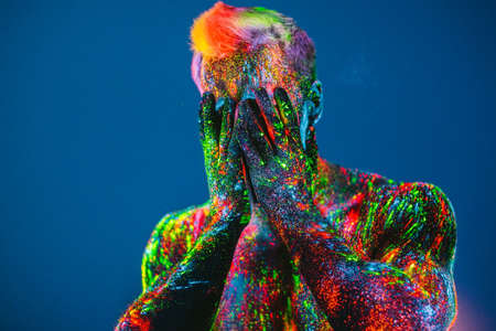The man is decorated in a ultraviolet powder