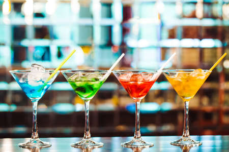 Multicolored cocktails at the bar. bartender show