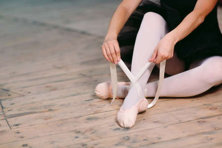 Young ballerina in black dress trains behind the scenes. Imagens