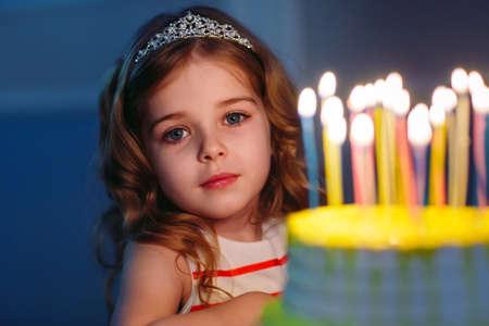 Childrens birthday. Children near a birthday cake with candles Standard-Bild