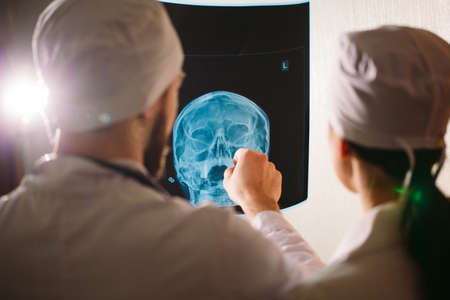 Doctors watching x-ray of patient near the hospital room. Stok Fotoğraf
