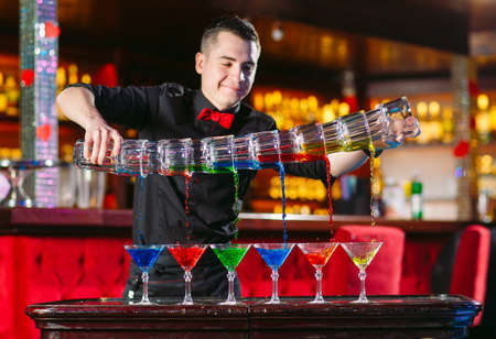 Barman show. Bartender pours alcoholic cocktails in a restaurant.