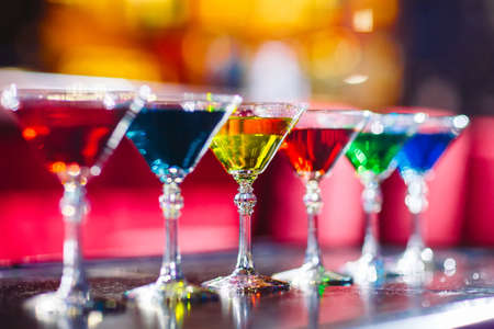 Multicolored cocktails at the bar on the wooden table. Foto de archivo