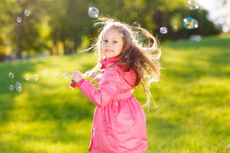 Die Mädchen laufen und spielen mit Seifenblasen. Standard-Bild