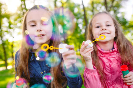 Girls play with soap bubbles in a spring time. 写真素材