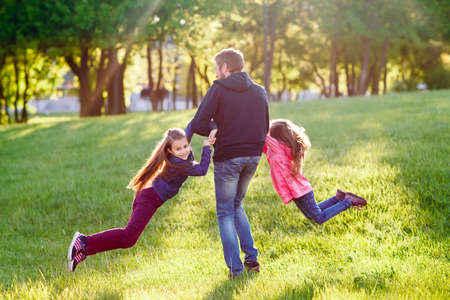 Father plays with daughters outdoors in a forest.