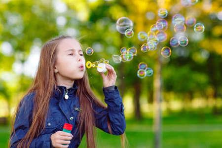 Die Mädchen laufen und spielen mit Seifenblasen.