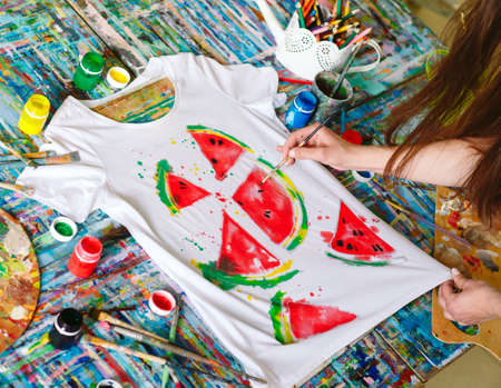 Drawing on clothes. Girl draws on a white T-shirt.