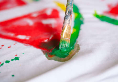 Drawing on clothes. Girl draws on a white T-shirt. 写真素材 - 131693329