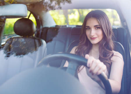 A young pretty girl is driving a car.