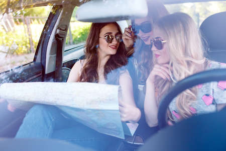 Three young girlfriends traveling in a car