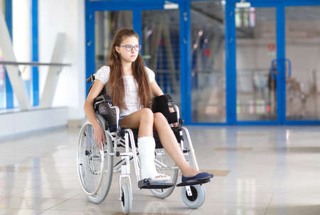 A young girl in a wheelchair is standing in the corridor of the hospital. 写真素材