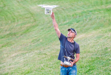 Young Man watching and navigating a flying drone.