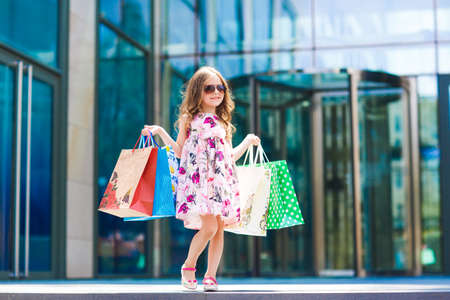 Cute little girl on shopping. Portrait of a kid with shopping bags. Shopping. girl Imagens