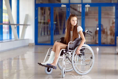 A young girl in a wheelchair is standing in the corridor of the hospital. Imagens