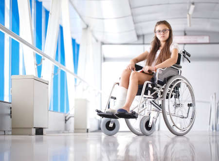 A young girl in a wheelchair is reading a book. Patient in a wheelchair in the hospital corridor