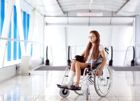 A young girl in a wheelchair is standing in the corridor of the hospital. Archivio Fotografico