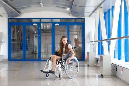 A young girl in a wheelchair is standing in the corridor of the hospital