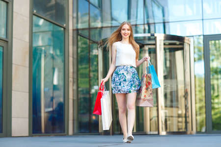 Lifestyle portrait young blonde girl, with shopping bags walking out from shop 写真素材 - 131693746