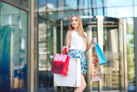 Lifestyle portrait young blonde girl, with shopping bags walking out from shop