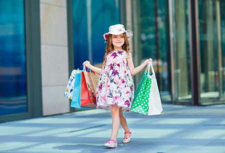 Cute little girl on shopping. Portrait of a kid with shopping bags. Shopping. girl 写真素材