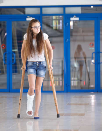 A young girl is on crutches in the corridor of the hospital