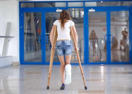 Una niña está con muletas en el pasillo del hospital. Foto de archivo