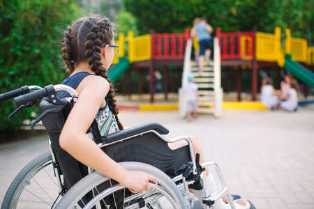 A girl with a broken leg sits in a wheelchair in front of the playground