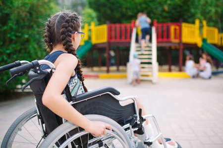 Een meisje met een gebroken been zit in een rolstoel voor de speeltuin Stockfoto