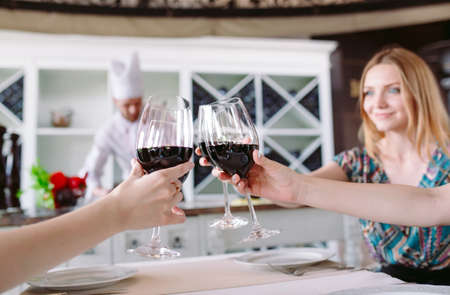 Young people in a restaurant drinking wine in the background a cook prepares Imagens