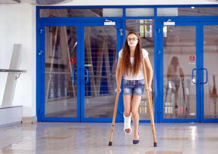 Une jeune fille est en béquilles dans le couloir de l'hôpital