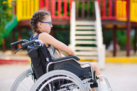 A girl with a broken leg sits in a wheelchair in front of the playground.