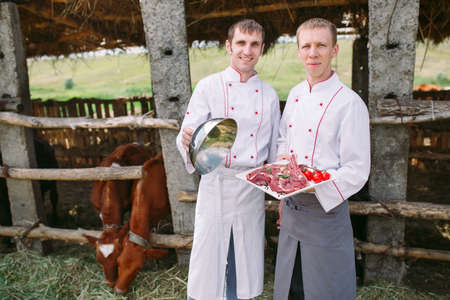 Cooks with a dish with a raw piece of meat on the background of a cowshed