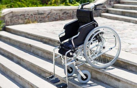 Wheelchair near the steps in a spring park. Reklamní fotografie