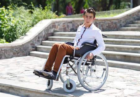A young man in a wheelchair who can not descend the stairs.