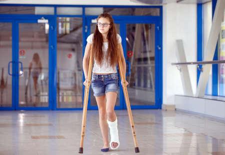 Une jeune fille est en béquilles dans le couloir de l'hôpital.