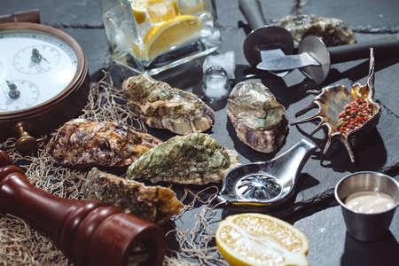 Huîtres sur plaque de pierre avec glace, citron, filet de pêche, poivre et couteau Banque d'images