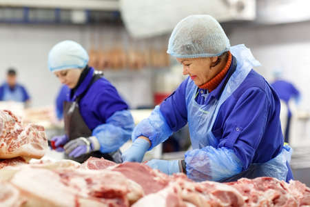 Cutting meat in slaughterhouse. The meat and sausage factory. Stock fotó