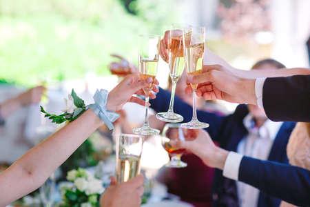 Hände, die Gläser halten und rösten, glücklicher festlicher Moment.