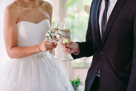 Bride and groom holding wedding champagne glasses Imagens
