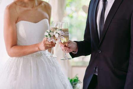 Sposa e sposo che tengono bicchieri di champagne da matrimonio
