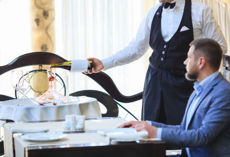 The sommelier pours the wine into the decanter near the guest in the restaurant Stock Photo