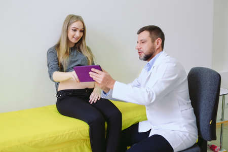 Gynecologist showing echo photo to pregnant woman.
