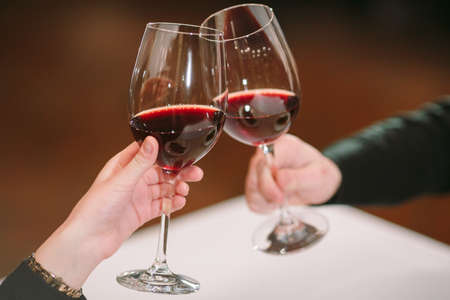 Man and woman drinking red wine. In the picture, close-up hands with glasses. 写真素材 - 131693282