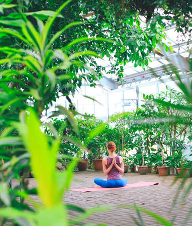 Portrait of gorgeous young woman practicing yoga indoor. Calmness and relax, female happiness.