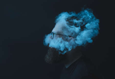 Concept. Smoke enveloped the head man. Portrait of a Bearded, stylish man with smoke. Secondhand smoke. 写真素材 - 131693269