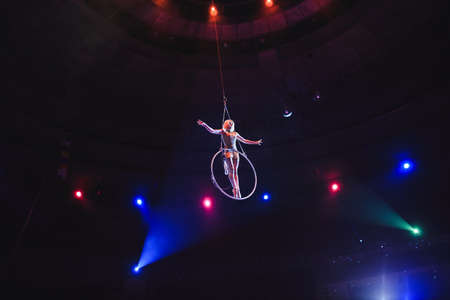 Aerial acrobat in the ring. A young girl performs the acrobatic elements in the air ring 写真素材 - 131694132