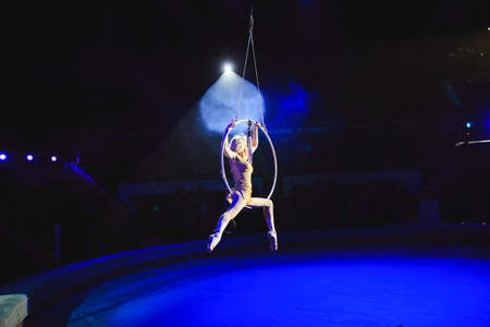 Aerial acrobat in the ring. A young girl performs the acrobatic elements in the air ring 写真素材