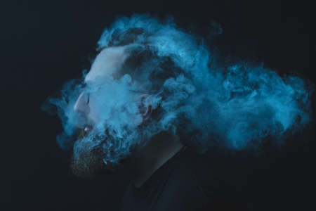 Concept. Smoke enveloped the head man. Portrait of a Bearded, stylish man with smoke. Secondhand smoke. 写真素材 - 131693601